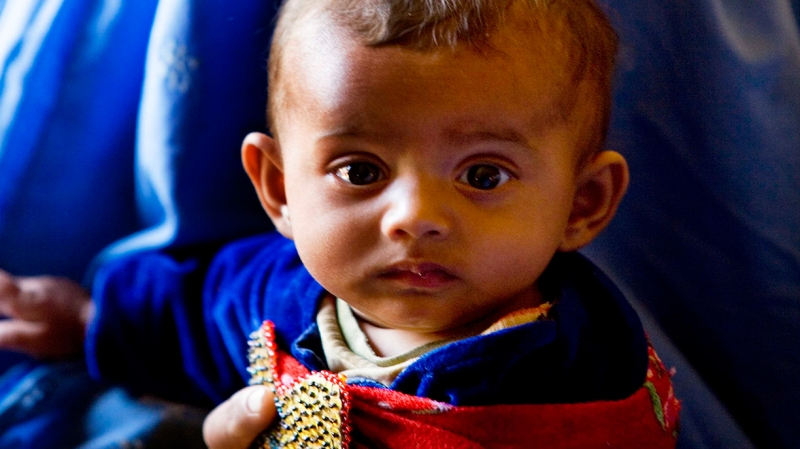 An Afghan child waits to receive healthcare.
