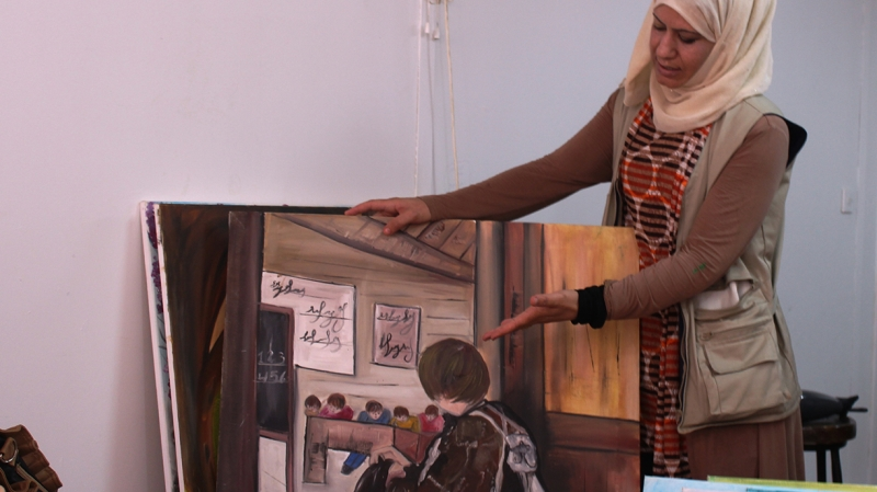 Israa showing a painting in zaatari youth programme