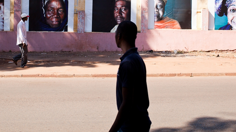 Passers by on this busy street can't help but notice these powerful portraits.. Credit: Vincent Tremeau/Oxfam