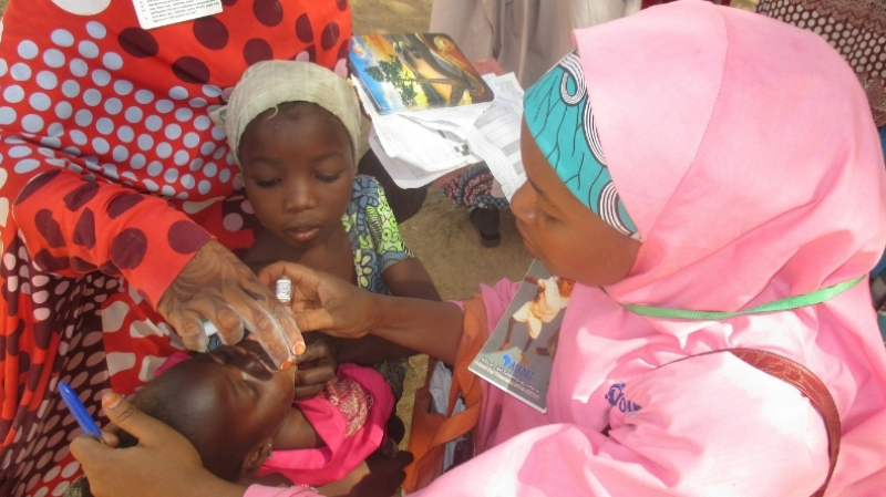 A child in Nigeria receives a polio vaccine during a campaign with the Core Group Polio Project.