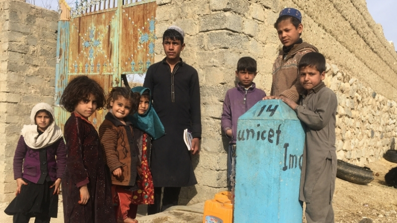 Children in Afghanistan stand next to a tap where they get clean water daily. With support from UNICEF, International Medical Corps constructed a solar-powered supply system that provides safe water to people in Nangarhar province.