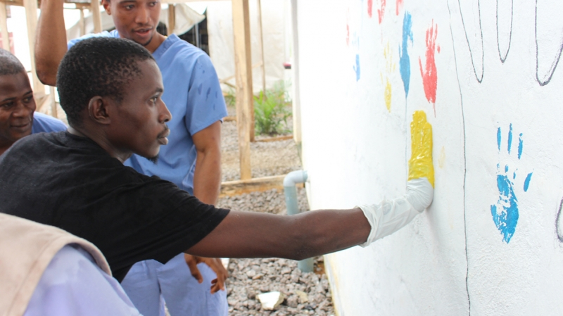 Alhaji leaves his handprint on the Ebola survivor wall in Sierra Leone