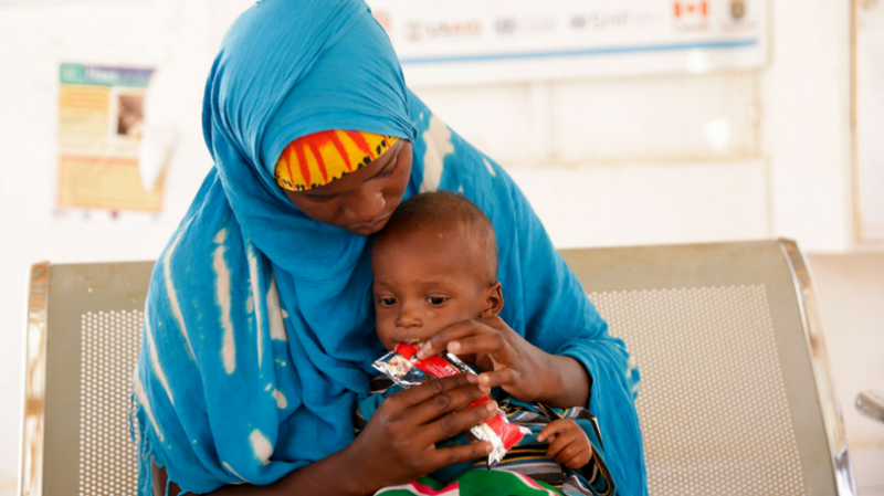 A mother feeds her severely malnourished child special therapeutic food provided at the hospital.