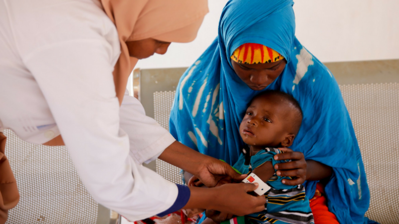 A nurse measures mid-upper arm circumference to screen a child for malnutrition.
