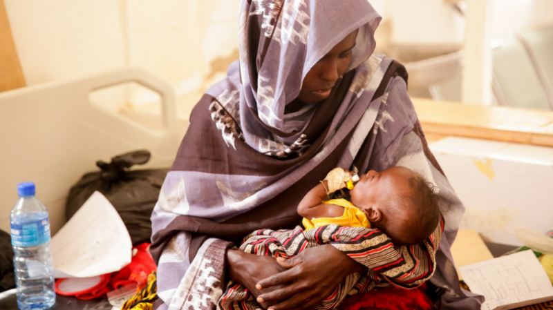 A Somali mother cradles her sick child, who is receiving treatment at the hospital.