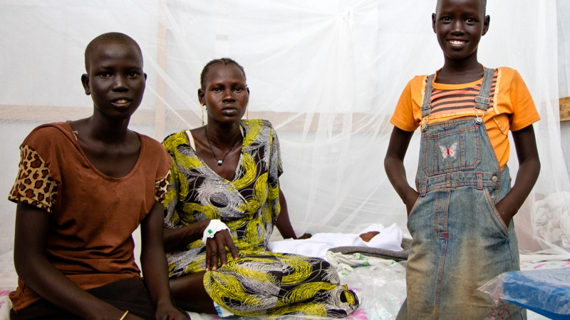 Nyawal (16, left) and Nyabana (10, right) are proud sisters of their newborn baby brother resting on the bed behind them in our Juba clinic South Sudan.