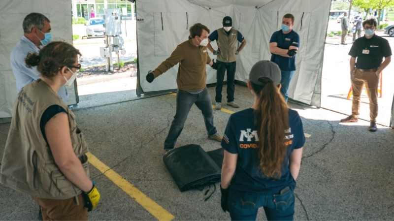 The International Medical Corps team prepares to move medical equipment into the tent to make it fully operational for serving patients.