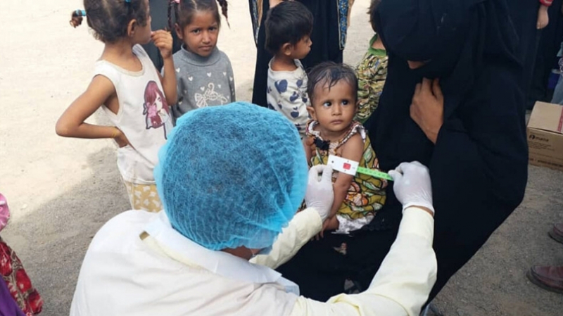 A member of International Medical Corps mobile medical unit measures a young child for malnutrition in a remote area of Sana'a Governorate.