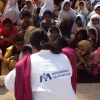An International Medical Corps doctor reassures children waiting to be immunised in Pakistan