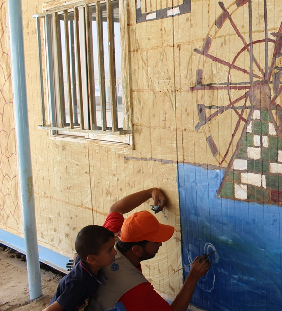 Syrian volunteers paint a mural at a child friendly space in refugee camp Jordan