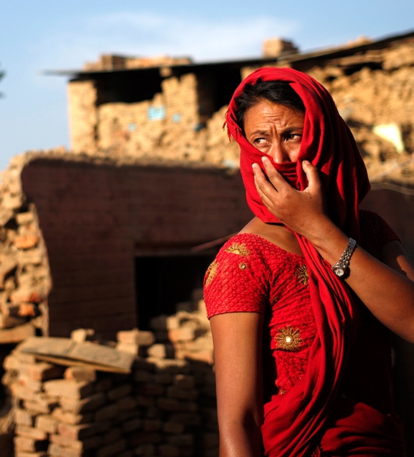 A woman stands by her home in Nepal